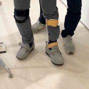 装具をつけて歩く四点杖の人と介助者