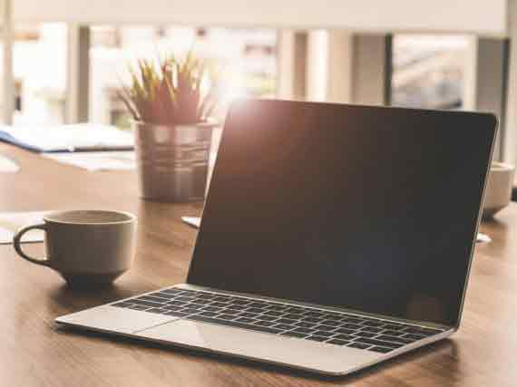 テーブルに置いてあるパソコンとコーヒーカップ