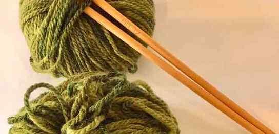 編み棒と緑の毛糸2個