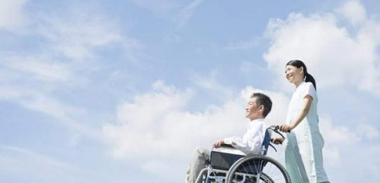 車いすに乗って屋外を介助してもらっている男性と介助者