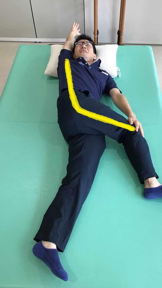 仰向けになり右ひざを立てて、その右ひざを左に倒して右手は万歳でストレッチ